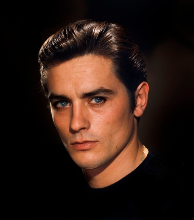 Photo studio : portrait de face souriant d'Alain DELON sur fond marron.
